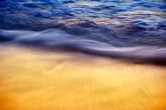 Abstract blue and golden silky ocean waves crashing on shore. royalty free stock photography
