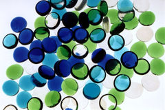 Abstract Blue Green. Blue, Green and Clear flat marbles on a lightbox stock images