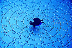 Abstract of a blue jigsaw with the last piece upstanding. Pieces fitting together in form of a spiral - adobe RGB Stock Photography