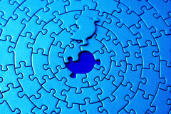 Abstract of a blue jigsaw with the missing piece laying above the space. Shallow DOF, focus is on the hole - adobe RGB Stock Photo