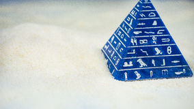 Abstract blue pyramid with hieroglyph staying on sand Royalty Free Stock Image