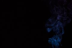 Abstract blue smoke on black Stock Images