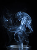 An Abstract Blue Smoke Flowing From Vertical Bottle Background Royalty Free Stock Image