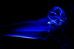 Abstract blue smoke swirls over black background Stock Photography