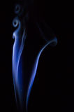 Abstract blue smoke swirls over black background.  Royalty Free Stock Photo