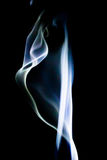 Abstract blue smoke swirls over black background Stock Image