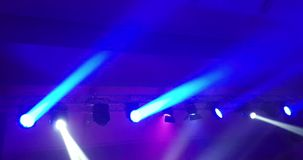 Abstract blue and violet purple, bright shiny stage lights flashing movement entertainment spotlight projectors in the dark