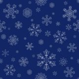 Abstract blue winter seamless pattern. Abstract winter seamless pattern with white snowflakes on dark blue background. Can be used for wallpaper, wrapping Stock Images