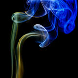 Abstract blue and yellow smoke from the aromatic sticks. Stock Photo