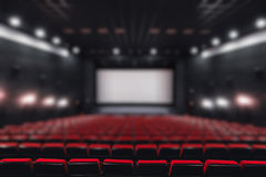 Abstract blur Empty rows of red theater or movie seats. Chairs in cinema hall. Comfortable armchair Stock Image