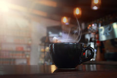Abstract blur hot black coffee in coffee shop with wooden table. Stock Image