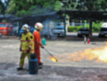Abstract blur people practicing how to stop fire in fire fighting training course. Safety first. Royalty Free Stock Photos
