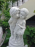Abstract blur statue of a young boy kissing a girl on the cheek. Royalty Free Stock Photos