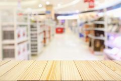 Abstract blur supermarket aisle with product shelves background. Wood table with Abstract blur supermarket aisle with product shelves background royalty free stock photo
