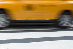 Abstract blur of urban street scene with a yellow taxi cab in Ne Royalty Free Stock Images