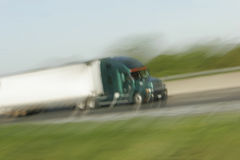 Abstract Blur White Trailer Truck. Abstract blur of trailer truck racing down country road with green grass below and pale blue sky above. Plenty of copy space stock images