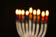 Abstract blurred background of jewish holiday Hanukkah background with menorah (traditional candelabra) Burning candles over black Royalty Free Stock Images