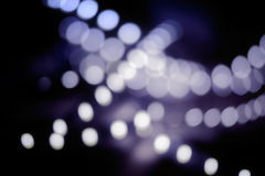 Abstract blurred blue bulbs lights background, blur of Christmas decorations in a dark, vintage colorized image Royalty Free Stock Photos