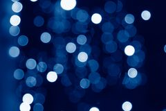 abstract blurred circular bokeh lights background toned in trendy Classic Blue color of the Year 2020