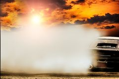 Abstract blurred drift car with smoke from burned tire at sunset.  stock photography