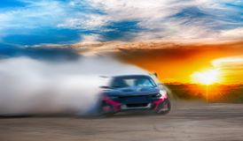 Abstract blurred drift car with smoke from burned tire at sunset royalty free stock photos