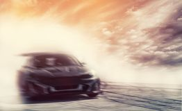 Abstract blurred drift car with smoke from burned tire at sunset.  royalty free stock images