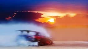 Abstract blurred drift car with smoke from burned tire at sunset.  royalty free stock photo