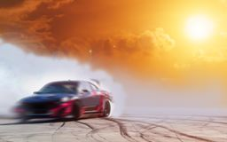 Abstract blurred drift car with smoke from burned tire at sunset.  stock photos