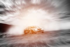 Abstract blurred drift cars with smoke from burned tire. At sunset Royalty Free Stock Image