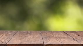 Green Leaves in the wind, a natural blurred background with a wooden old stationary table on a summer sunny day. Slow. Abstract blurred green background out of stock video footage