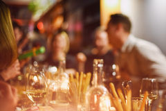 Abstract blurred group of friends meeting in the restaurant. Blurry background of caucasian people having fun, eating Royalty Free Stock Image
