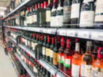 Abstract blurred image. Defocused lens. Wine, cognac and other alcoholic beverages on the shelves in the supermarket stock image