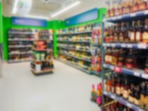 Abstract blurred image. Defocused lens. Wine, cognac and other alcoholic beverages on the shelves in the supermarket royalty free stock images