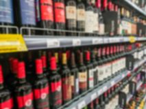Abstract blurred image. Defocused lens. Wine, cognac and other alcoholic beverages on the shelves in the supermarket royalty free stock image