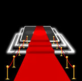 Abstract blurred image. Red carpet with stairs between two rope barriers and flash light. Scene illuminated by a spotlight. Royalty Free Stock Images