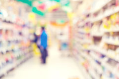 Abstract blurred interior of supermarket with people shopping background Stock Images