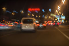 Abstract blurred moving white car and fast driving traffic at night in city, bright brake lights Royalty Free Stock Photo