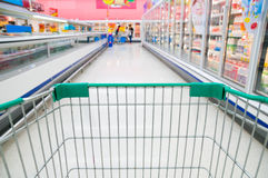 Abstract blurred photo of store with trolley in Supermarket stor Royalty Free Stock Images