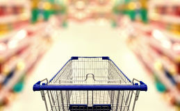 Abstract blurred photo of  supermarket with empty shopping cart. Shopping concept Royalty Free Stock Photos