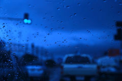 Abstract blurred scene of Road view through car window with rain drops. Stock Image