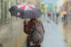 Abstract blurred silhouette of girl under umbrella, city street seen through raindrops on window glass, blurred motion Royalty Free Stock Image