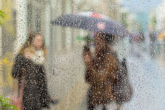 Abstract blurred silhouettes of people with umbrellas on rainy day in city, two girls seen through raindrops on window Royalty Free Stock Photos
