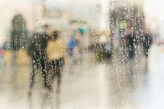 Abstract blurred silhouettes of people with umbrellas on rainy day in city, two persons seen through raindrops on window Stock Images