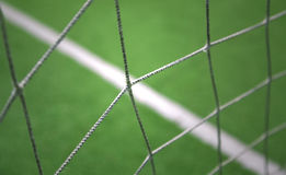 Abstract blurred soccer goal net background. Abstract blurred soccer goal net closeup with soccer field background. Selective focus used Stock Photos