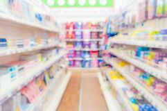 Abstract blurred supermarket aisle with colorful shelves and unrecognizable customers as background. School supplies royalty free stock images