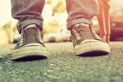Abstract blurred urban background,low angle photo of pavement texture and person's shoes. selective focus Royalty Free Stock Image