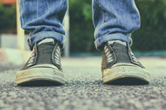 Abstract blurred urban background,low angle photo of pavement texture and person's shoes. selective focus Royalty Free Stock Images