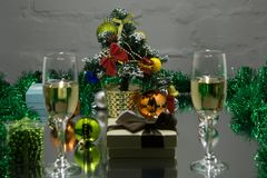 Abstract blurry background :Christmas or New Year. Champagne in glasses with candles, panettone and gift with red satin bow. Copy- Stock Photography