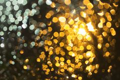 Abstract bokeh: Background light blurred, Orange from the water droplets, front of the car Stock Photos