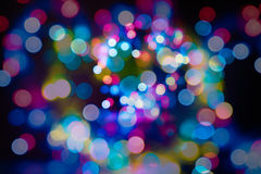 Abstract bokeh on black background with blur and flare made from different colours. Glitter bokeh on black. Stardust explosion spa Stock Photos